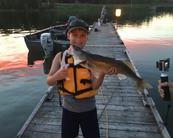 Happy young man caught this 25 inch walleye off the dock